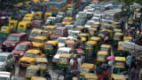 Indian commuters cross the road amid heavy rush hour traffic in Kolkata on July 31, 2015.